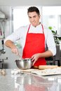 Smiling chef mixing batter in bowl to prepare portrait of male ravioli pasta commercial kitchen Stock Photography