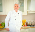 Smiling chef senior in his kitchen Stock Photography
