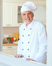 Smiling chef senior in his kitchen Stock Images