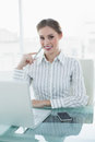 Smiling chic businesswoman sitting at her desk in front of laptop and smartphone looking camera Stock Photography