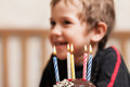 Smiling child with birthday cake candle little boy blowing celebration sweet fire Royalty Free Stock Image