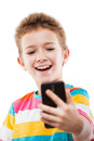 Smiling child boy holding mobile phone or smartphone taking self Royalty Free Stock Photo