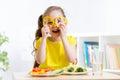 Smiling child eating in kindergarten girl eats vegan food having fun Stock Photography
