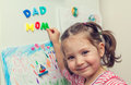 Smiling child forms mom dad words on refrigerator closeup photograph of hand forming and with magnetic letters door Stock Image