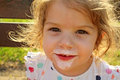 Smiling child the girl ate an ice cream because of this smudged her mouth her face joy visible Stock Photography