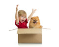 Smiling child with hands up and dog in cardbox isolated on white background