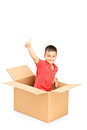 Smiling child in a paper box giving thumb up and looking at came camera isolated on white background Royalty Free Stock Images