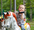 Smiling child riding a toy horse carousel Royalty Free Stock Photo