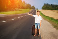 Smiling child with suitcase traveling hitchhiking summer road Royalty Free Stock Photography