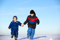 Smiling children running on snow together outdoors in winter Royalty Free Stock Photos