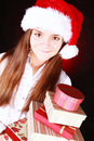 Smiling christmas girl holding presents over dark Royalty Free Stock Images
