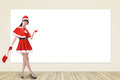 Smiling christmas woman show something on blank white wall full length portrait Stock Photo