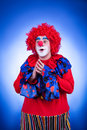 Smiling clown on blue background studio shooting professional lighting Royalty Free Stock Photo