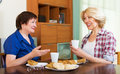 Smiling colleagues drinking tea and talking during pause for lun two in years lunch Royalty Free Stock Photo
