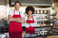 Smiling colleagues in red apron with arms crossed at the bakery Royalty Free Stock Photos
