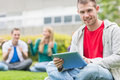 Smiling college boy holding tablet pc with students in park portrait of a blurred sitting the Royalty Free Stock Images