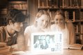 Smiling college friends watching photos on digital interface in university library Royalty Free Stock Images