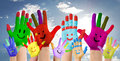Smiling colorful hands raised up against clouds background Royalty Free Stock Photography