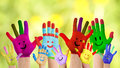 Smiling colorful hands raised up against green background Royalty Free Stock Photography
