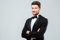 Smiling confident man in tuxedo standing with arms crossed Royalty Free Stock Photo