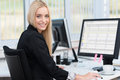 Smiling confident young business woman sitting at her desk in front of a desktop computer turning to smile at the camera Royalty Free Stock Photos