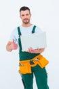 Smiling construction worker holding laptop on white backboard Stock Image