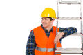 Smiling construction worker with ladder in yellow helmet and orange waistcoat looking at copy space waist up studio shot isolated Stock Photography