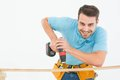 Smiling construction worker using hand drill on wooden plank portrait of against white background Stock Images