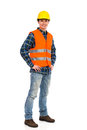 Smiling construction worker waiting in yellow helmet and orange waistcoat full length studio shot isolated on white Stock Photo