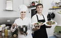 Smiling cook giving to waitress ready to serve salad Royalty Free Stock Photo