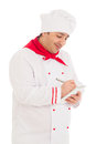 Smiling cook man whriting something in notebook with pen wearing red and white uniform the studio over white background Royalty Free Stock Photography