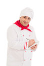 Smiling cook man writing something in notebook with pen wearing red and white uniform the studio over white background Stock Images