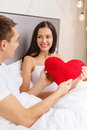 Smiling couple in bed with red heart shape pillow hotel travel relationships holidays and happiness concept shaped Stock Photos