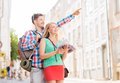 Smiling couple with city guide and backpack travel vacation friendship concept in Royalty Free Stock Image