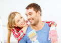 Smiling couple covered with paint with paint brush repair building and home concept Royalty Free Stock Image