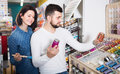Smiling couple examining various paints in paint store Royalty Free Stock Photo