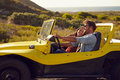 Smiling couple going on holidays together on a summer day young men with his girlfriend road trip in buggy car Stock Images