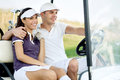 Smiling couple in golf cart driving Royalty Free Stock Image