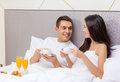 Smiling couple having breakfast in bed in hotel travel relationships and happiness concept room Royalty Free Stock Photography