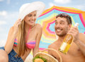 Smiling couple having picnic on the beach Royalty Free Stock Photo