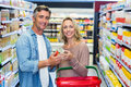 Smiling couple holding canned food Royalty Free Stock Photo
