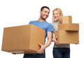 Smiling couple holding cardboard boxes moving home and family concept Stock Images