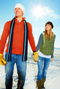 Smiling couple holding hands out on the snow Stock Images