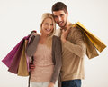 Smiling couple holding shopping bags studio shot of a caucasian Stock Images