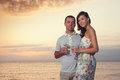 Smiling couple holding wineglasses during sunset on the beach of sea or ocean Stock Image
