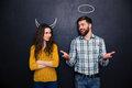 Smiling couple imitating devil and angel over chalkboard background Royalty Free Stock Photo