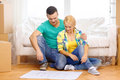 Smiling couple looking at bluepring in new home moving and concept relaxing on sofa and blueprint Stock Images