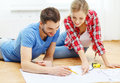 Smiling couple looking at blueprint at home repair building renovation and concept Stock Image