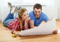 Smiling couple looking at blueprint at home repair building renovation and concept Royalty Free Stock Photography