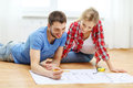 Smiling couple looking at blueprint at home repair building renovation and concept Stock Photos